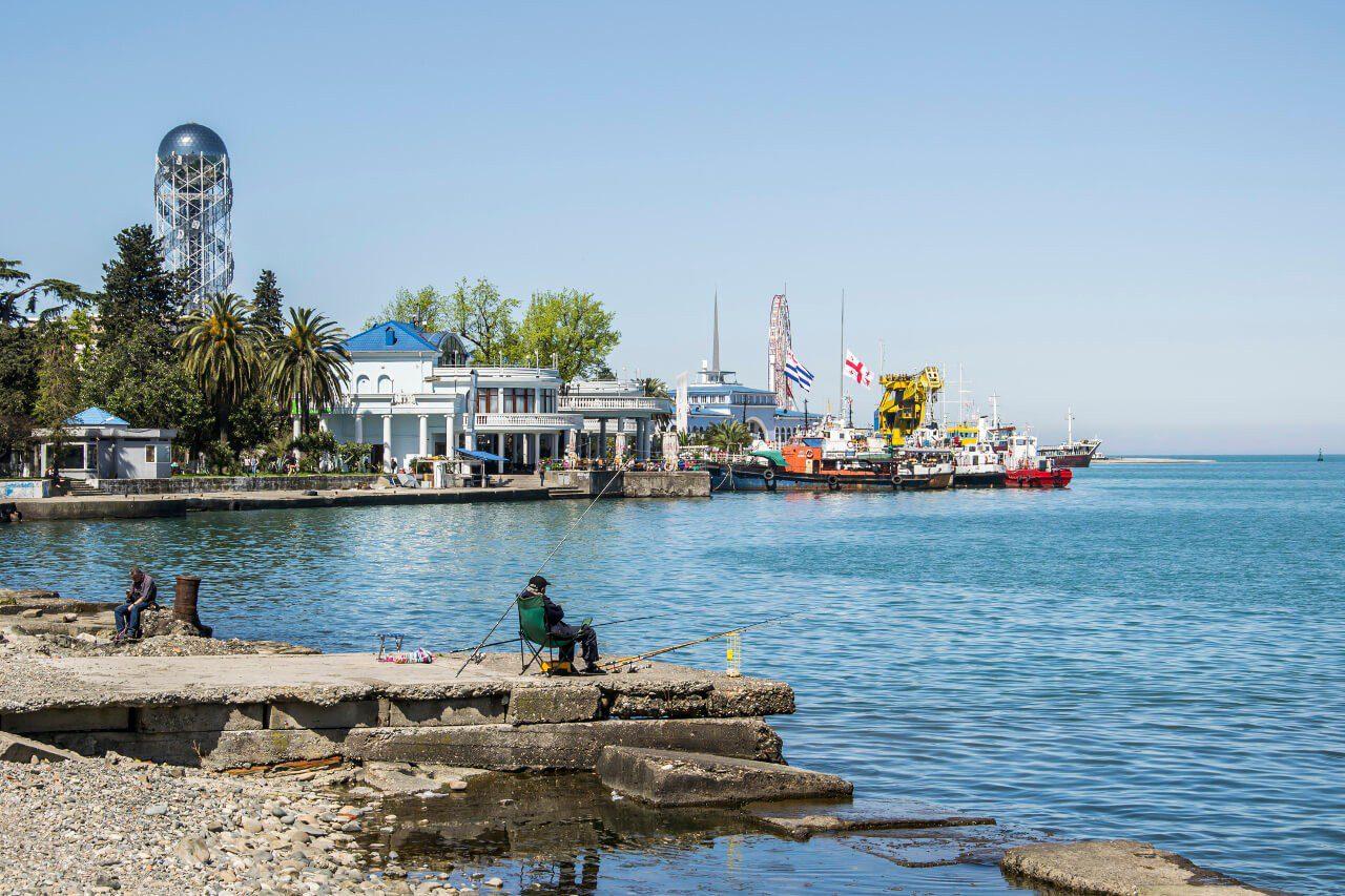 Wędkarz przy porcie w Batumi, w tle Wieża Alfabetu