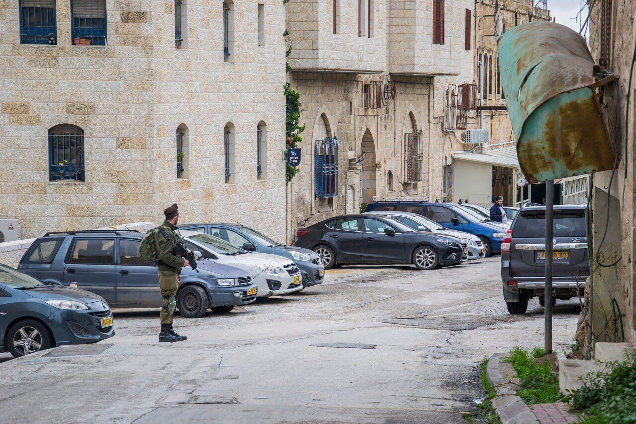 Uzbrojony wartownik przy jednym z punktów kontrolnych na Al-Shuhada w Hebronie.