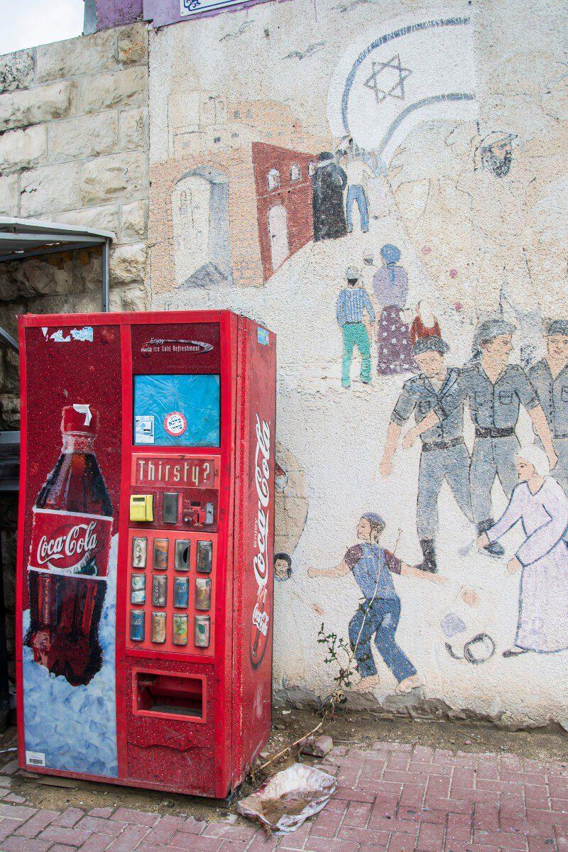 Murale i stary dystrybutor z Coca Colą przy dawnym dworcu autobusowym w Hebronie.