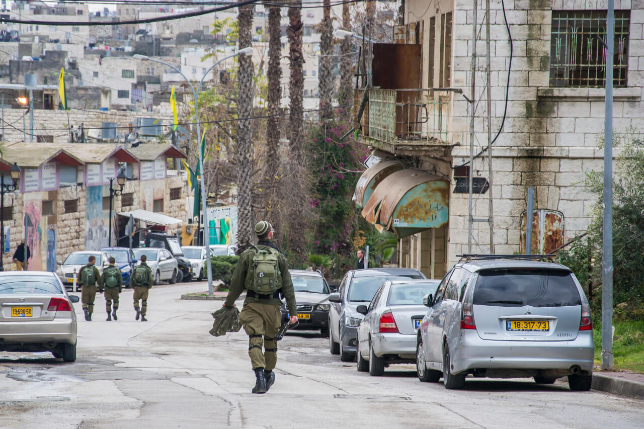Izraelscy żołnierze, patrolujący ulicę Al-Shuhada w Hebronie w strefie kontrolowanej przez Izrael, kierują się do bazy wojskowej.