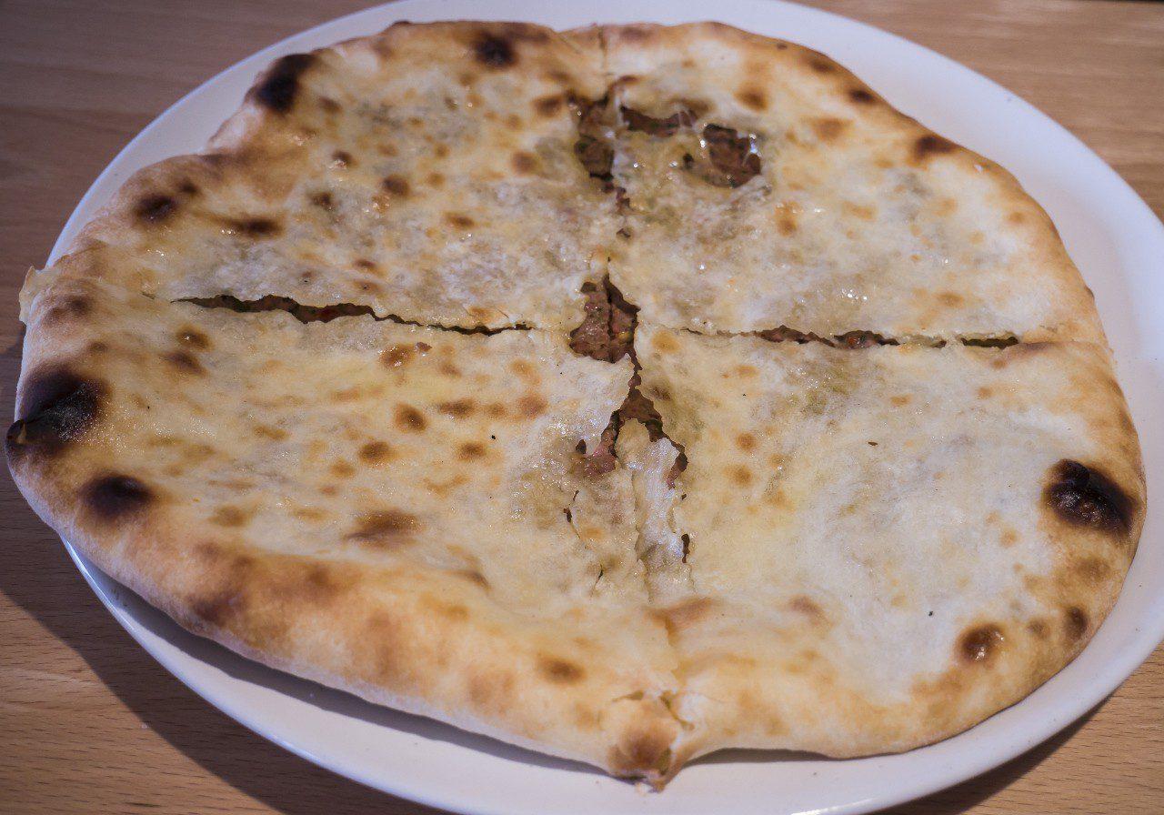 Placek kubdari wypełniony mięsem na talerzu