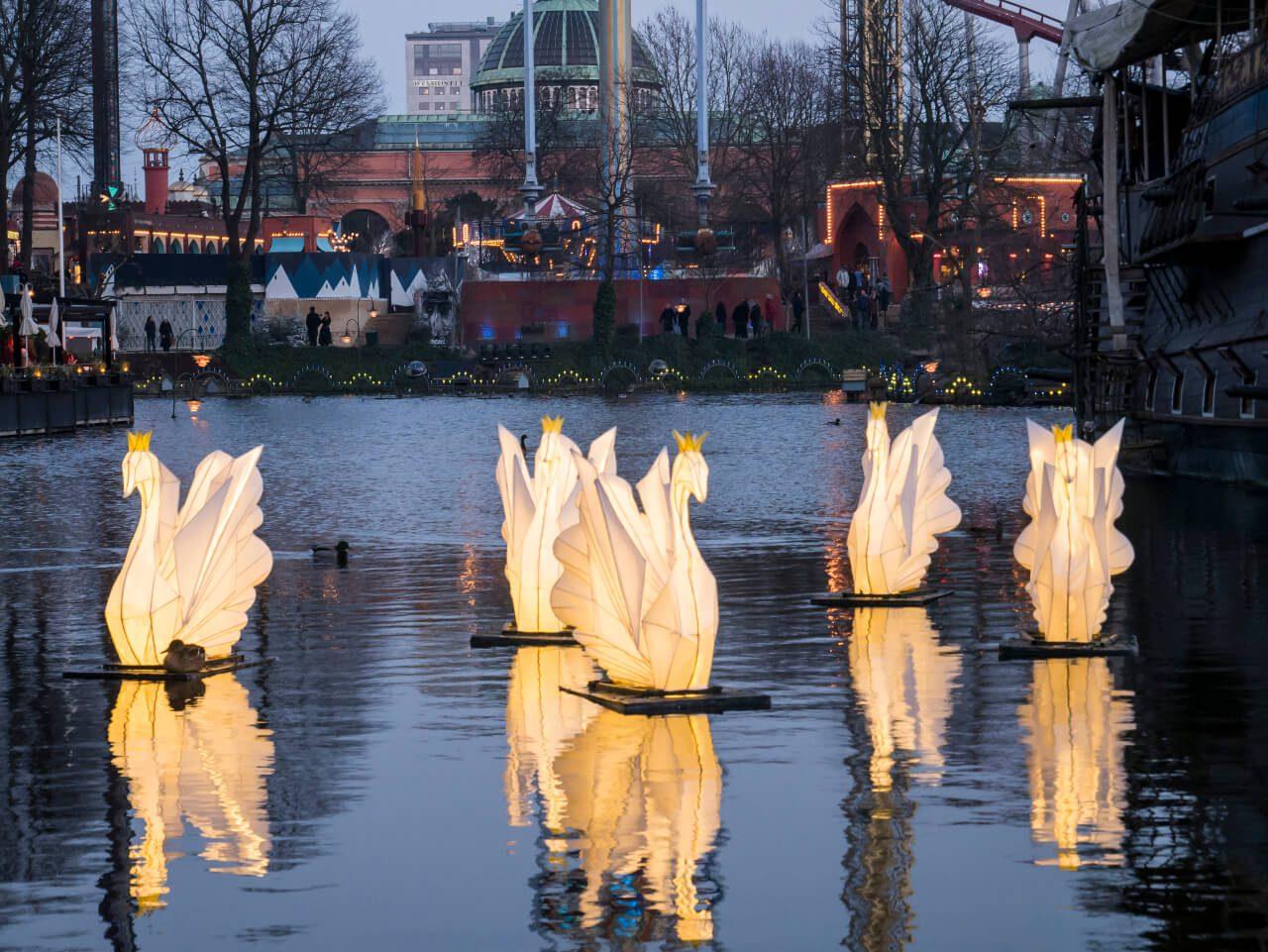 Oświetlone łabędzie na jeziorze w parku Tivoli