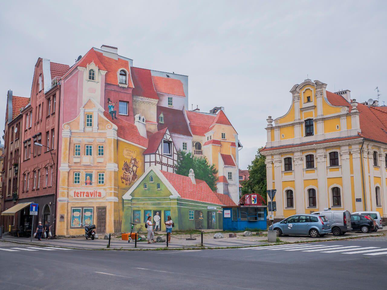 """Mural """"Opowieść śródecka z trębaczem na dachu i kotem w tle"""" w Poznaniu"""