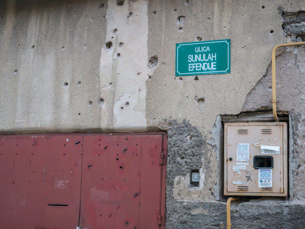 Ślady po kulach i wybuchach na ulicy Sunulah Efendije w Sarajewie