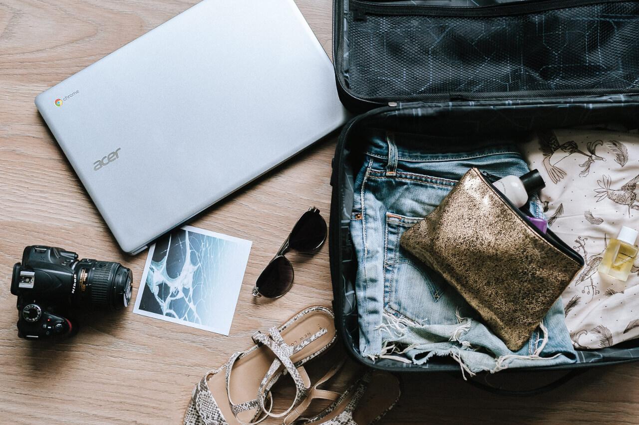 Pakowanie przed podróżą komputer, walizka, rzeczy